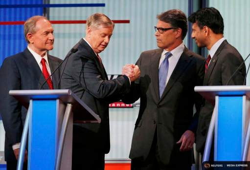 Republican presidential candidates, former Virginia Governor Jim Gilmore (L) and Louisiana Governor Bobby Jindal (R) look on as fellow candidates, U.S. Senator Lindsey Graham (2nd from L) and former Texas Governor Rick Perry, clasp hands as they talk in the midst of a break at a Fox-sponsored forum for lower polling candidates held before the first official Republican presidential candidates debate of the 2016 U.S. presidential campaign in Cleveland, Ohio, August 6, 2015. REUTERS/Brian Snyder