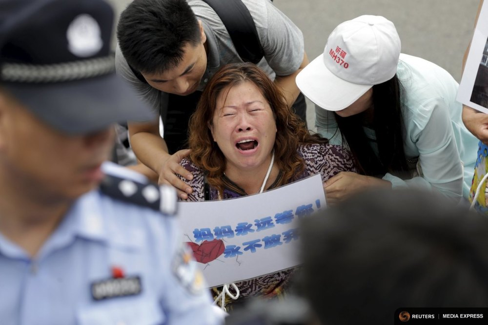 "A woman whose relative was aboard Malaysia Airlines flight MH370, holds a placard that reads, ""Mom is always here waiting for you, never will give up"", as she cries next to family members and kneels down in front of media ahead of a briefing given by Malaysia Airlines, in Beijing August 7, 2015. REUTERS/Jason Lee"